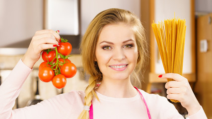 Woman holding pasta and tomatoes
