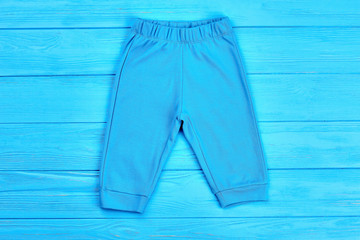 Infant boy cotton pants isolated. High quality cotton pants for baby-boy, blue wooden background. Brand clothes for kids on sale.