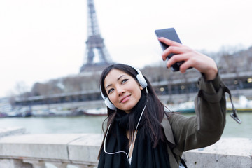 Pretty asian young woman taking a selfie in front of Eiffel tower in Paris while listening to music.