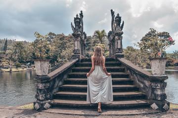 beautiful girl with long dark hair in elegant grey dress posing in Tirta Gangga water temple in Bali