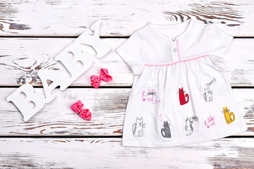Baby-girl summer clothes background. Infant baby cat print cotton dress, pink bows, text baby on white wooden background.
