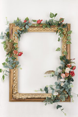 Empty old decorative frame braided with curly roses, hanging on the wall