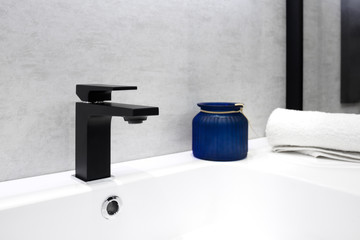Gray bathroom interior with white sink black modern techno style faucet blue glass jar and white towel