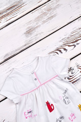 Baby-girl white brand dress. Infant girl beautiful natural dress on white wooden background, top view.
