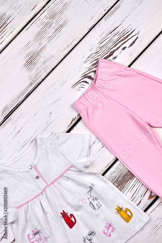 f8ccc8a3eec9e Set of new clothes for kids. Baby-girl top and trousers on white wooden  background, top view. Toddler girls fashion summer outfit.