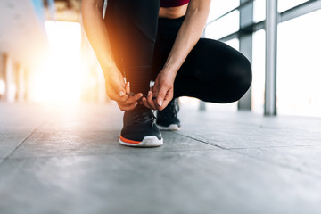Sport lifestyle. Close-up of female runner tying shoelace.