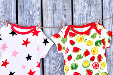Kids modern clothes hanging on rope. Infants printed apparel drying on clothesline on old wooden background.