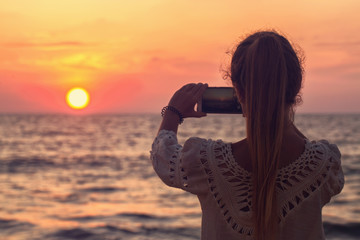 A girl takes a picture of the sunset