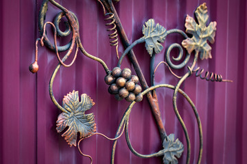 Forged bunch of grapes. ornate wrought-iron elements of metal gate decoration