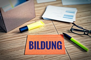 Index cards with legal issues with glasses, pen and bamboo with the german word Bildung in english education
