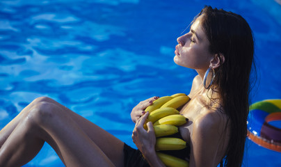 woman with tropical fruit in pool. Vitamin in banana at girl sitting near water. Summer vacation and travel to ocean. Dieting and healthy organic food, vegetarian. Woman relax in spa pool.
