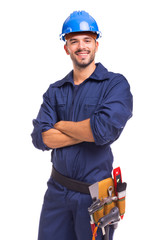 Portrait of a confident young worker standing with arms crossed on white background