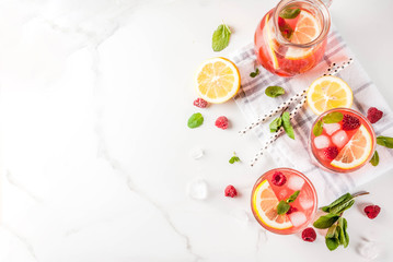 Summer refreshing drinks, fruit and berry raspberry mojito or lemonade with fresh mint, frozen raspberries, slices of lemon, ice, on a light background. copy space top view