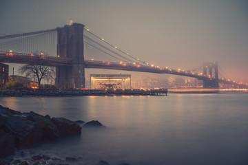 Fotomurales - Brooklyn bridge and Manhattan at foggy evening, New York City