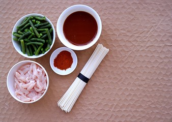 Ingredients for cooking wok-noodles in Chinese style. Dry wheat noodles, green beans, chicken, soy sauce, sweet ground pepper