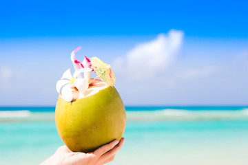 delicious fresh coconut cocktail with umbrella in hand