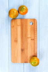 Background with fresh orange-green mandarines on the cutting board