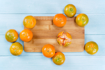Fresh orange-green mandarines on the blue table