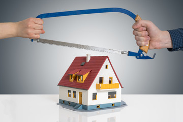 Divorce and dividing a house concept. Man and woman are splitting model of house with saw. Fotomurales