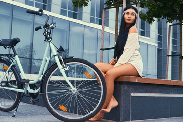 Portrait of a sexy hippie female wearing blouse and shorts in a headband, sits barefoot on a bench near city bike against a skyscraper