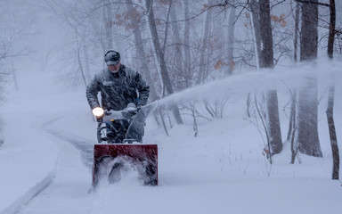 A man is removing snow using snowblower