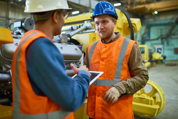 Two young technicians wearing reflective vests and hardhats using digital tablet while discussing how to solve problems with workflow, interior of spacious production department on background