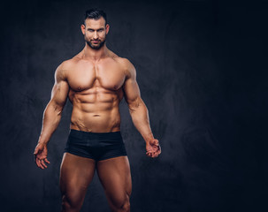 Portrait of a shirtless tall huge male with a muscular body with a stylish haircut and beard, in a underwear, posing in a studio.