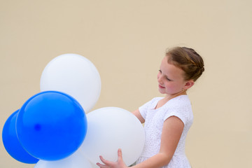 55aead31d Little girl playing with balloons outdoor. Happy child wears white ...