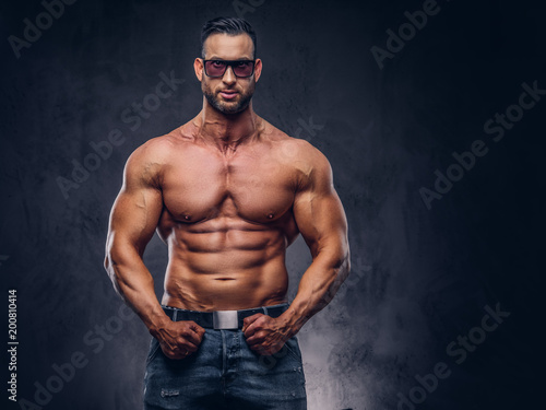 portrait of a shirtless tall huge male with a muscular body with a