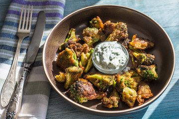 Fried broccoli in batter with spicy white sauce in a plate on a rustic background - top view