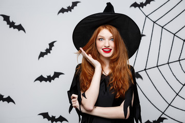 Halloween Concept - Beautiful caucasian witch surprising with something over grey background.