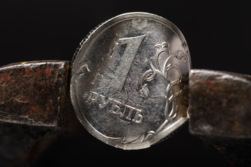 Russian ruble is clamped in a vice. Image on a black background