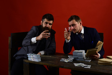 Company celebrates business profit, successful deal. Businessmen discussing illegal deal while drinking and smoking, red background. Men sitting at table with piles of money. Business success concept.
