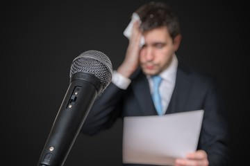 Microphone in front of a nervous man who is afraid of public speech and sweating. Wall mural
