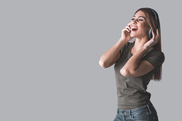 Portrait of young attractive female person finding enjoyment in song playing in her headset. She is singing. Copy space in left side. Isolated on background