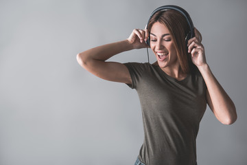 Portrait of satisfied woman enjoying melody via earphones. She is moving and looking down. Isolated on background