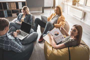Tranquil men and women sitting with comfort in their modern office. Girl with project documentation in hand looking at camera while her partners using gadgets