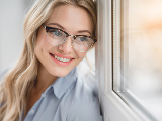 Portrait of happy blond businesswoman enjoying view from the window and smiling