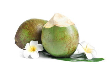 Fresh green coconuts with flowers on white background