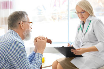 Mature doctor consulting patient at home