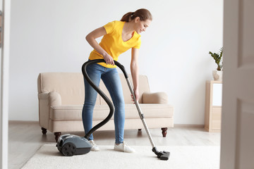 Young woman cleaning carpet with vacuum in living room