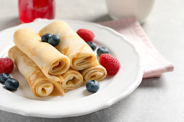 Thin pancakes with berries on plate