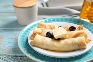Thin pancakes with berries and butter on plate, closeup