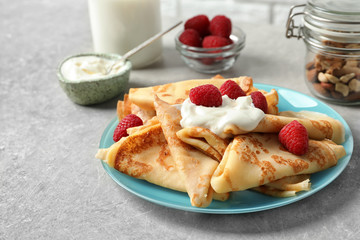 Thin pancakes with berries and sour cream on plate, closeup