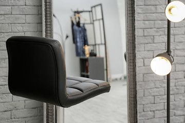 Comfortable chair near mirror in makeup room