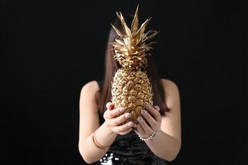 Woman holding golden pineapple on dark background