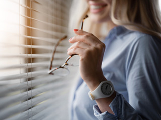 Close up of young woman arm holding eyeglasses while standing near window. Focus on watch on her wrist