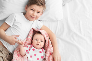 Cute little baby with elder brother lying on bed at home Wall mural
