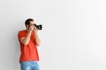 Young photographer with professional camera on white background