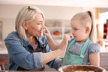 Little girl and her grandmother having fun with flour in kitchen